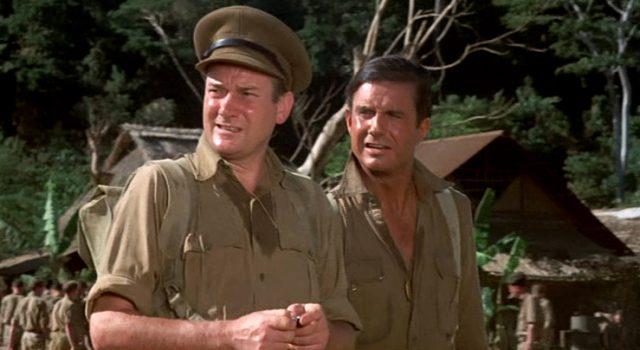 Captain Hornsby (Denholm Elliott) und Lieutenant Sam Lawson (Cliff Robertson) stehen verschwitzt im britischen Lager, Copyright: ABC Motion Pictures