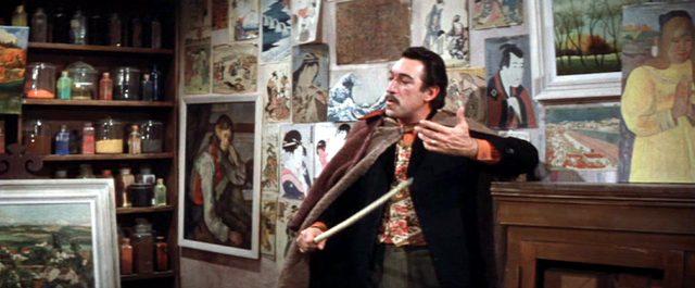 Paul Gauguin (Anthony Quinn) steht in einem Zimmer, dessen Wand mit Gemälden plakatiert ist, Copyright: Turner Entertainment