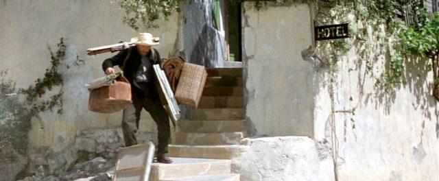 Van Gogh (Krik Douglas) schleppt sich vollbepackt mit seinem Malerei-Equipment die Außentreppe eines Gebäudes hinunter, Copyright: Turner Entertainment