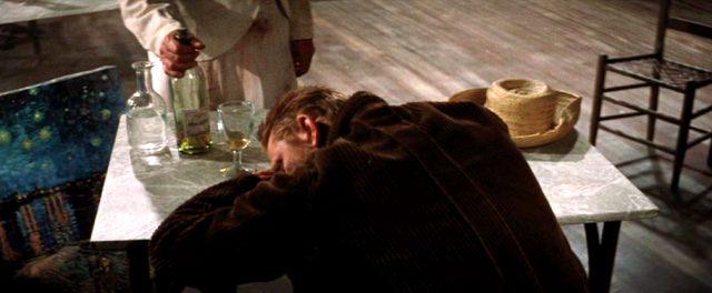 Van Gogh (Kirk Douglas) liegt zusammengesunken auf dem Tisch einer Kneipe, nebem ihm eine Spirituosenflasche