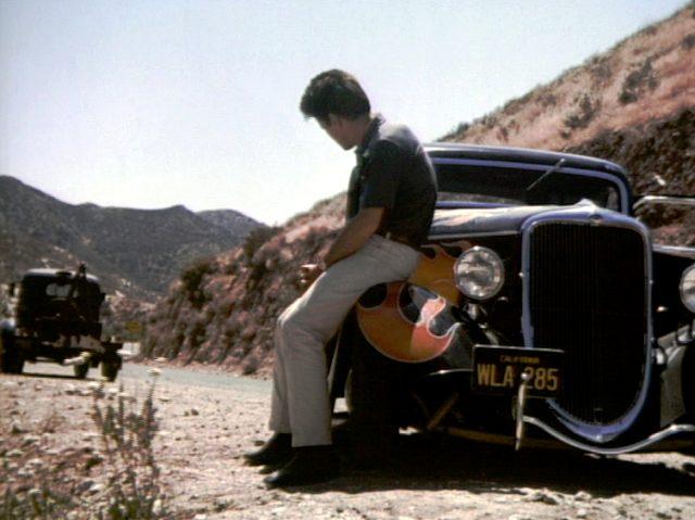 Michael McCord (Martin Shee) lehnt an seinem Fahrzeug und beobachtet einen Abschleppwagen