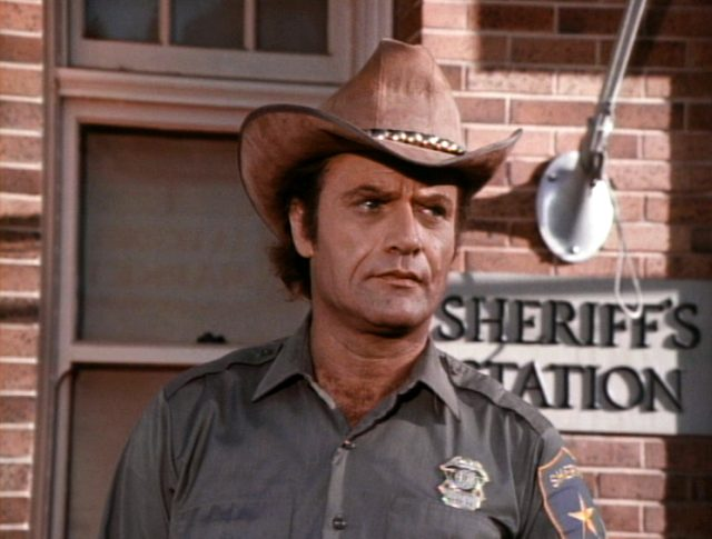 Sheriff Roy Childress (Vic Morrow) steht mit Hut und in Uniform vor der Sheriff's Station, Copyright: Universal