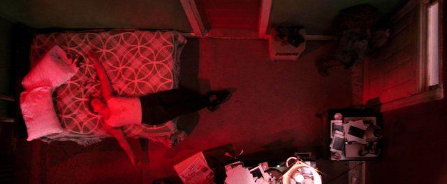 ein Appartement aus der Vogelperspektive; auf dem Bett liegt ein bewusstloser Mann, an der Tür steht eine Frau