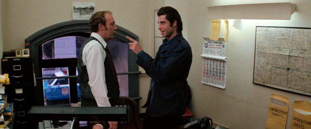 Jack Terry (John Travolta) im Gespräch mit einem Polizeikommissar (John Aquino), Copyright: Viscount Associates