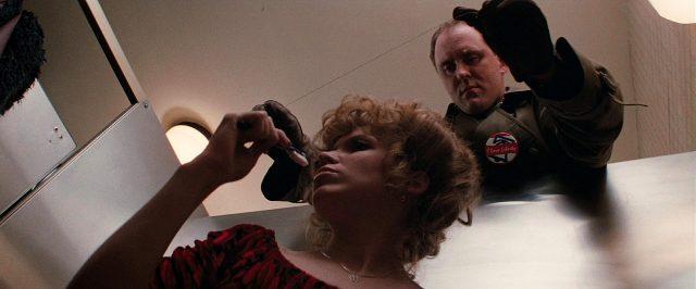 Killer Burke (John Lithgow) versucht eine Frau in der Toilettenkabone zu erdrosseln, Copyright: Viscount Associates