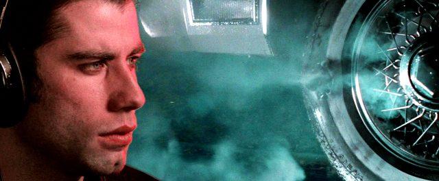 Splitscreen, der auf der linken Seite Jack Terry (John Travolta) und auf der rechten Seite den von einem Projektil beschädigten Autoreifen zeigt