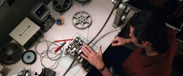 Jack Terry (John Travolta) arbeitet an einem Tisch mit diversen Geräten