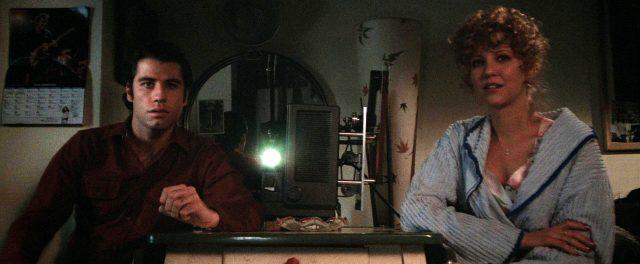 Jack (John Travolta) und Sally (Nancy Allen) sitzen neben einem Projektor, der einen Film abspielt