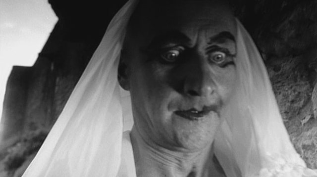 Donald Pleasence als George, der hier gerade einen Schleier trägt und im Gesicht geschminkt ist