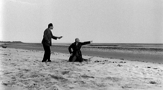 Dick bedroht George am Strand mit einer Waffe, Copyright: Compton-Tekli Film