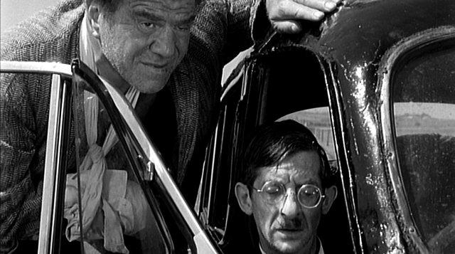Lionel Stander als Gangster Dick mit verbundenem Arm und Jack MacGowran als schwer verletzter Gangster Albie an ihrem defekten Auto