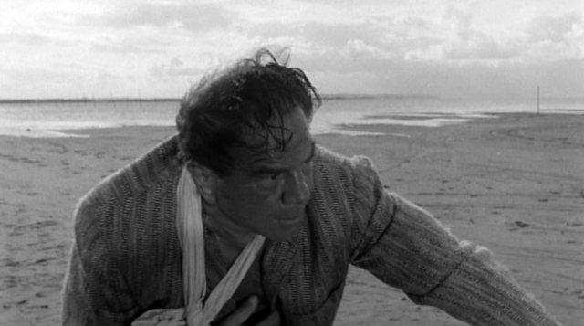 Lionel Stander als Gangster Richard, der mit verbundenem Arm am Strand steht
