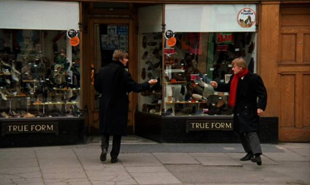 Malcom McDowell und David Wood tollen auf dem Bürgersteig der Innenstadt vor einem Laden herum
