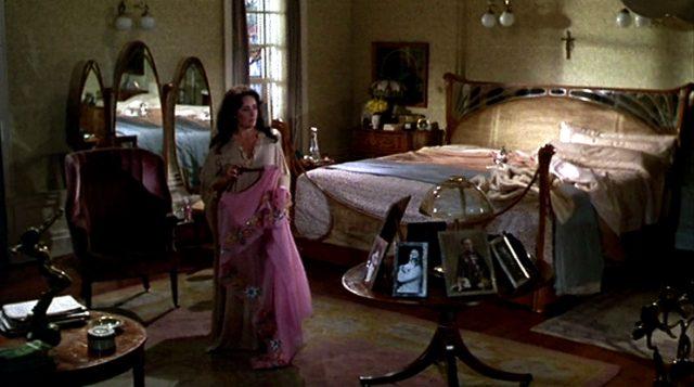 Leonora (Elizabeth Taylor) steht inmitten des mit luxuriösen Gegenständen gefüllten Schlafzimmers