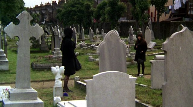 die beide in Schwarz gekleideten Leonora (Elizabeth Taylor) und Cenci (Mia Farrow) stehen sich an einem Grab auf einem Londoner Friedhof gegenüber, Copyright: Universal