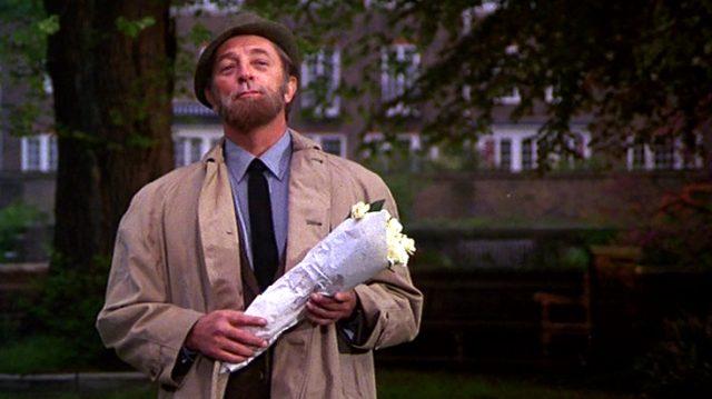 Robert Mitchum als Stiefvater Albert, der mit einem Strauß Blumen im Garten wartet, Copyright: Universal