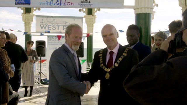 Richie Beckett (Peter Mullan) posiert mit dem Bürgermeister von Brighton bei der Feier für sein Pier-Projekt vor Pressekameras, Copyright: World Productions
