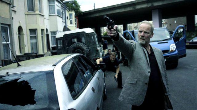Richie Beckett (Peter Mullan) mit ausgestreckter Waffe inmitten einer Schießerei