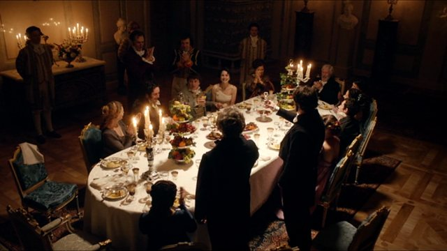 Eine aristokratische Adelsgesellschaft sitzt bei Kerzenlicht an einer großen Tafel; einer der Teilnehmenden hat sich zu einem Toast erhoben.