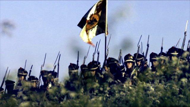 Eine Gruppe Soldaten marschiert während der Schlacht zwischen Russen und Franzosen in geordneter Formation einen Hang hinab.