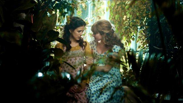 Die beiden Aristokratinnen Sonya und Natasha Rostova (Aisling Loftus und Lily James) sitzen im Wintergarten auf einer Bank.