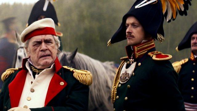 Brian Cox als russischer General Kutuzov mit sorgenvollem Blick im Beisein eines Offiziers an der Front.