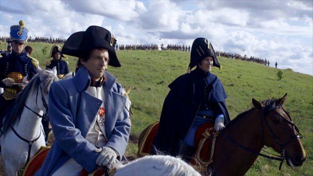 Napoleon (Mathieu Kassovitz) blickt, im Beisein einiger Offiziere, zu Pferd in Richtung des Schlachtfeldes; im Hintergrund steht auf einer Anhöhe die Linieninfanterie seiner Armee.