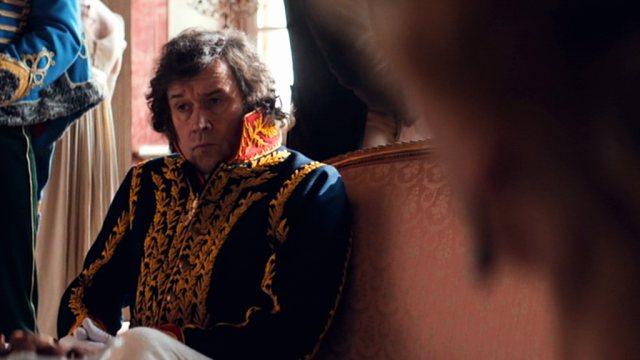 Stephen Rea als Prinz Vassilly Kuragin mit bedächtigem Blick inmitten einer Salon-Gesellschaft.