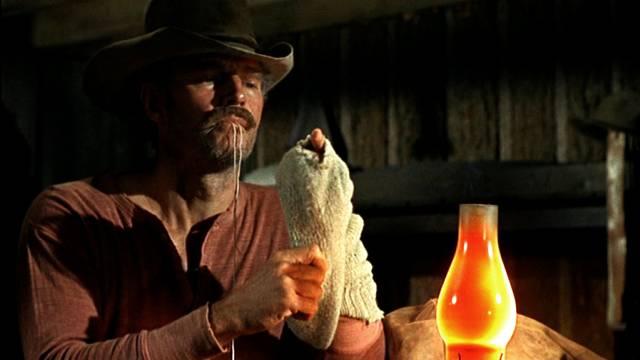 Charlton Heston als Cowboy, der eigenhändig seine Socken stopft