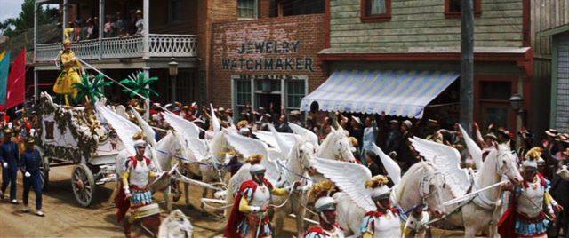Zirkusparade in einer Kleinstadt mit einer weißen Kutsche, die von Schimmeln mit angebrachten Kunstschwingen gezogen wird