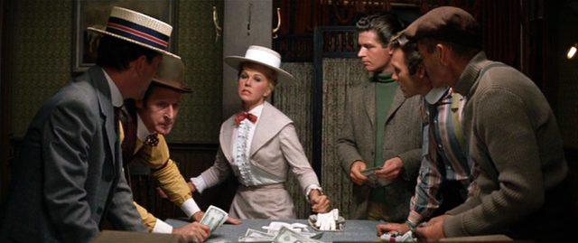 Kitty Wonder (Doris Day) in einer Männerrunde beim Würfelspiel, neben ihr steht der Artist Sam (Stephen Boyd)