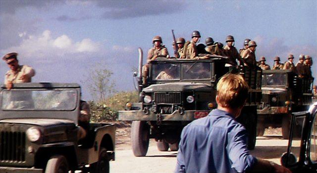 Batista-Truppen fahren auf einer Straße mit Trucks und einem Geländewagen an Jack Weil vorbei