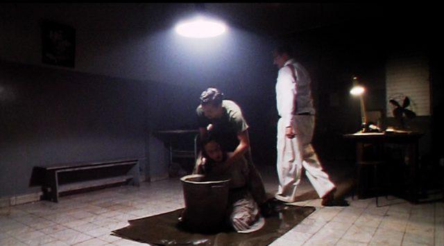 zwei Männer foltern jemanden in einem düsteren Raum