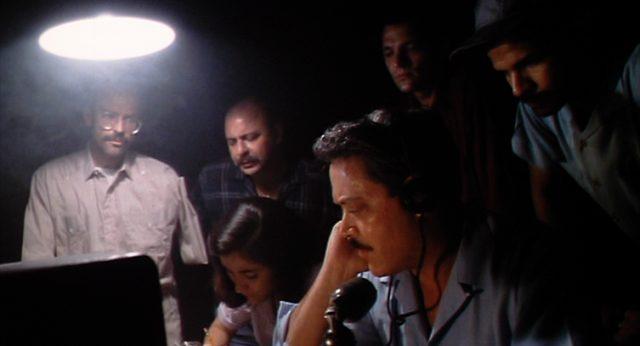 kubanische Revolutionäre (u.a. Arturo Duran, gespielt von Raul Julia) in einem dunklen Raum