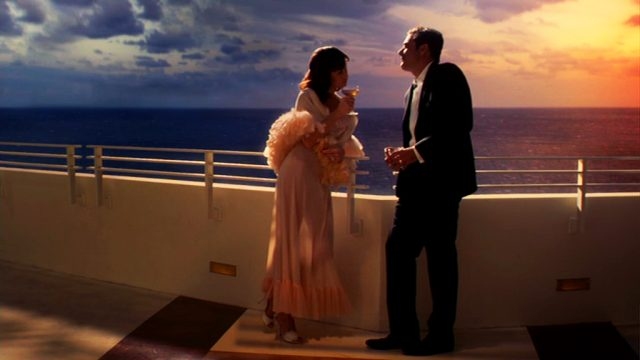 Ike und Vera Evans stehen an der Brüstung eines Hotelbalkons vor romantischem Horizont