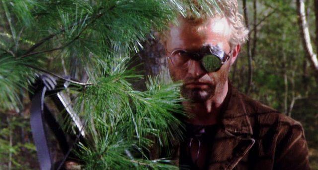 Jim Malden (Rutger Hauer) mit Armbrust im Gebüsch, Copyright: Hemdale, Sagittarius, Orion