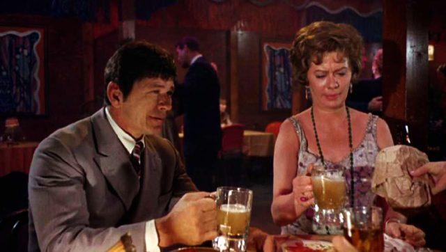 J.J. Nichols (Charles Bronson) und Hazel Starr (Kate Reid) sitzen an einem Tisch und trinken Bier