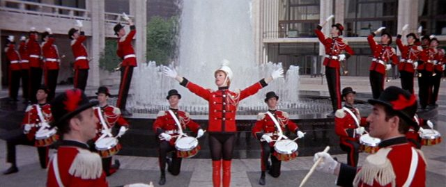 Charity (Shirley MacLaine) vor einem großen Springbrunnen, umgeben von uniformierten Tänzern
