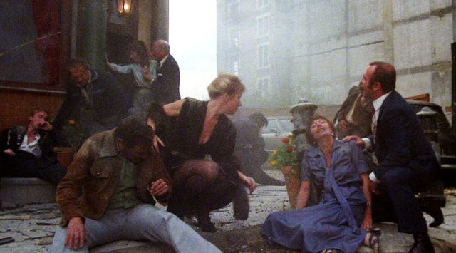 Victoria (Helen Mirren) und Harold (Bob Hoskins) zusammen mit anderen Personen vor dem zerstörten Gebäude unmittelbar nach der Explosion, Copyright: HandMade Films
