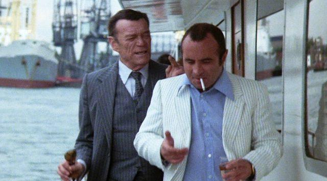 Harold Shand (Bob Hoskins) an Deck seiner Yacht auf der Themse im Gespräch mit einem Geschäftspartner