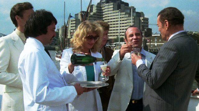 Harold Shand (Bob Hoskins) steht mit seinen Geschäftspartnern an Bord seiner Yacht, während ihm Victoria (Helen Mirren) Champagner einschenkt, Copyright: HandMade Films