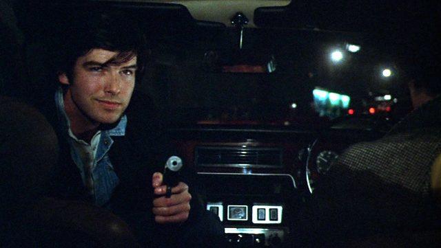 Pierce Brosnan als Killer mit vorgehaltener Waffe in einem Fahrzeug