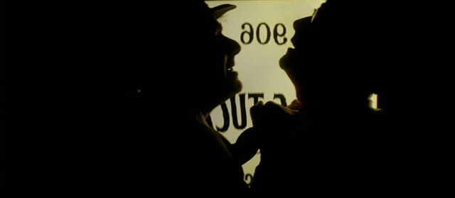 Silhouetten zweier Männer vor einer teilverglasten Tür