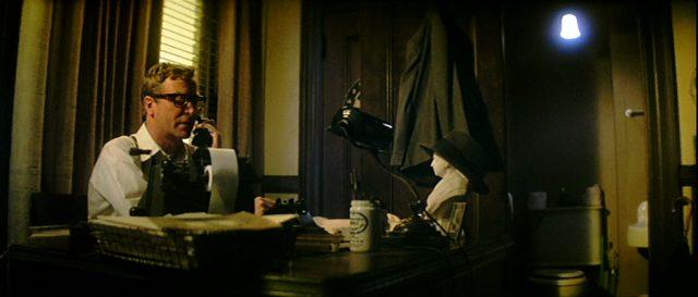 Leslie C. Tucker (Michael Caine) sitzt in seinem düsteren Büro am Schreibtisch und telefoniert