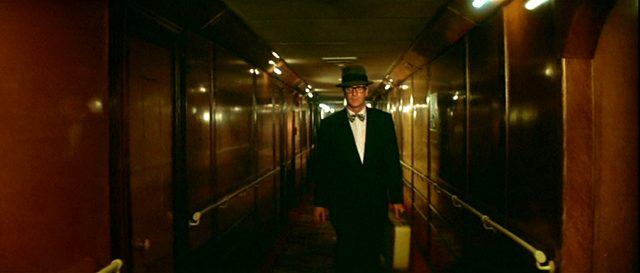Leslie C. Tucker (Michael Caine) geht mit einem Koffer in der Hand durch einen Gang