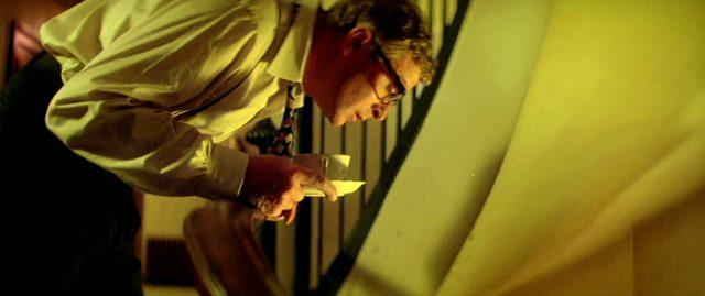 Leslie C. Tucker (Michael Caine) bückt sich mit einer Tasse in der Hand in einem Treppenhaus