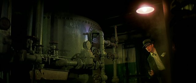 Leslie C. Tucker (Michael Caine) mit vorgehaltener Pistole in einem schwach beleuchteten Raum