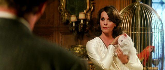 Ellen Prandergast (Natalie Wood) steht neben einem goldenen Vogelkäfig und streichelt eine weiße Katze, die sie auf ihrem Arm trägt