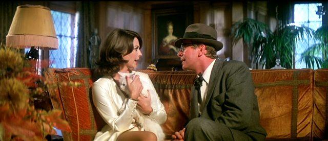 Ellen Prandergast (Natalie Wood) und Leslie C. Tucker (Michael Caine) unterhalten sich auf einem Samt-Sofa