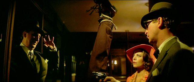 Leslie C. Tucker (Michael Caine) bedroht einen Mann mit einer Pistole, neben ihm steht Ellen Prandergast (Natalie Wood)